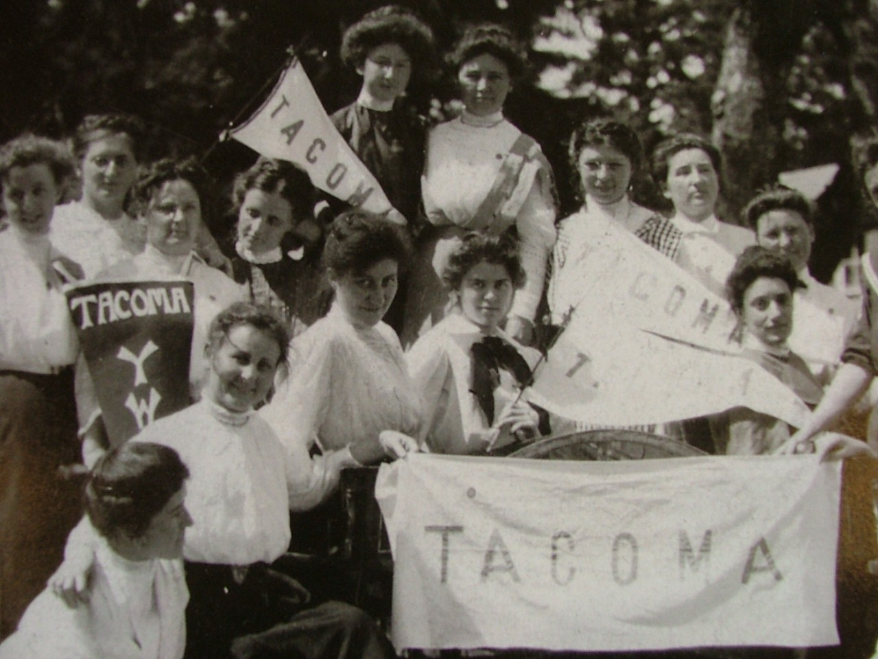 Women from 1906 charter of YWCA in Tacoma holding YWCA banners